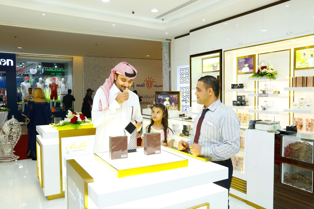 Delighted customer smelling top fragrances at Al Haramain Perfumes Seef Mall Bahrain